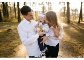 一对年轻夫妇带着一个小男孩走在树林里_3280576