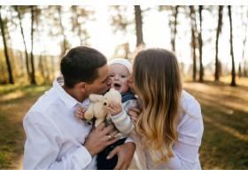 一对年轻夫妇带着一个小男孩走在树林里_3280577