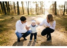 一对年轻夫妇带着一个小男孩走在树林里_3280578