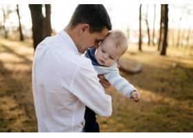 一对年轻夫妇带着一个小男孩走在树林里_3280582