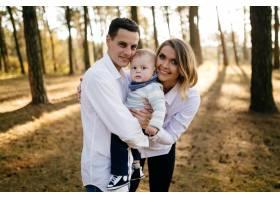 一对年轻夫妇带着一个小男孩走在树林里_3280583