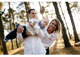 一对年轻夫妇带着一个小男孩走在树林里_3280584