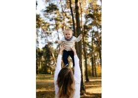 一对年轻夫妇带着一个小男孩走在树林里_3280585