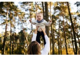 一对年轻夫妇带着一个小男孩走在树林里_3280586