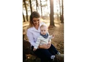 一对年轻夫妇带着一个小男孩走在树林里_3280588