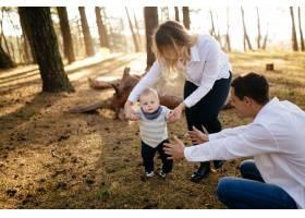 一对年轻夫妇带着一个小男孩走在树林里_3280589