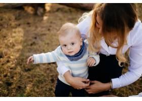 一对年轻夫妇带着一个小男孩走在树林里_3280590