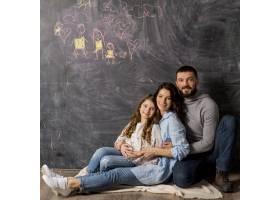 父母带着女儿在黑板附近拥抱手里拿着画_4112385