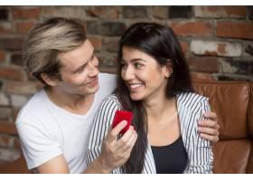 男子在家中向兴奋的女子求婚手持戒指盒_3938889