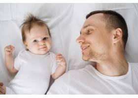 英俊的爸爸躺在床上抱着可爱的婴儿_4856709