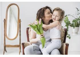 美丽的母亲在家里抱着一束郁金香花亲吻她的_4040665
