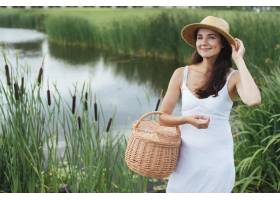 美丽的母亲拿着野餐篮在湖边摆姿势_4962072