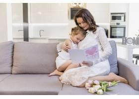 美丽的母女坐在客厅的沙发上读贺卡_4057014