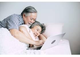 老年夫妇在卧室里使用笔记本电脑_4107933