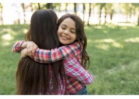 闭着眼睛微笑的可爱女孩在公园拥抱她的母亲_4958768