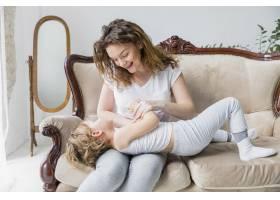 顽皮的母女俩在家里的沙发上玩耍_4048278