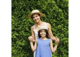 母女俩在灌木丛前摆姿势_4962276