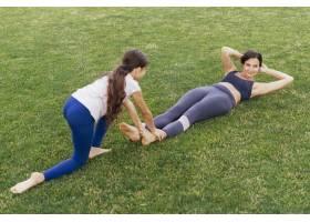 母女俩在绿草地上锻炼身体_4962264