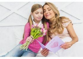 母女俩坐在一起手里拿着鲜花和贺卡_4029973