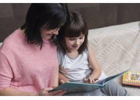 母女俩坐在沙发上看书_3967189