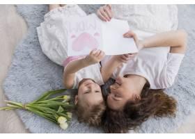 母女俩躺在蓝色毛茸茸的地毯上上面有鲜花_4048422