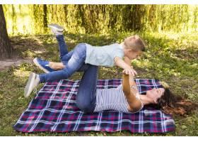 母子俩在野餐毯上玩耍_5149480