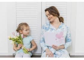 漂亮的小女儿和妈妈拿着贺卡和一束郁金香相_4040647