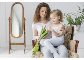 漂亮的母女俩坐在家里的扶手椅上_4040671