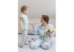 漂亮的母女俩手持鲜花在床上看着对方_4040529