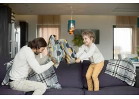 父亲和小儿子在客厅里的枕头大战_3938160