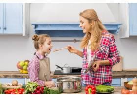 微笑的女人在厨房里用木勺给女儿品尝食物_4400046