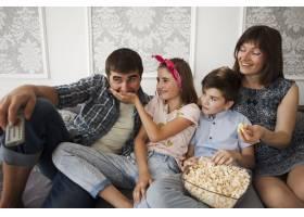 微笑的女儿和家人坐在沙发上给父亲喂爆米花_5127623