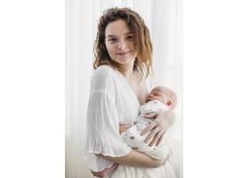 微笑的母亲在白色窗帘前抱着孩子的肖像_4056867