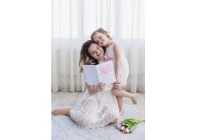 微笑的母女俩在家里一起看母亲节贺卡_4048461