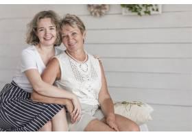 微笑的母女坐在沙发上看相机的肖像_5044000