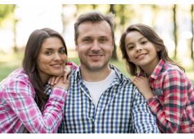 微笑的男人和他的妻子和女儿在公园里看着相_4958787
