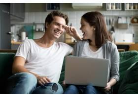 快乐的千禧一代夫妇一起在厨房沙发上使用笔_3953892