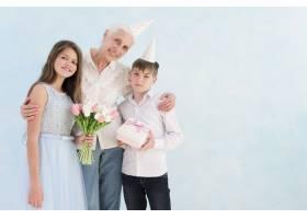 快乐的孩子们与祖母手持鲜花花束和礼盒的_4929789