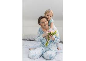 快乐的年轻女子在床上抱着一束郁金香花载着_4040521