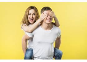 快乐的年轻女子在黄色背景下骑在男朋友的背_3911834
