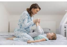 快乐的年轻母亲在床上陪女儿玩耍_4040551