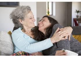 快乐的年长母亲和她的女儿在家里的沙发上放_4166912