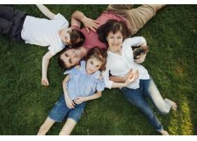 快乐的父母和孩子躺在公园的草地上_5098273