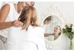成熟的女人看着坐在镜子前的母亲_5061064