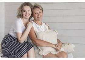 成熟的微笑母亲抱着垫子和她美丽的女儿坐在_5043979