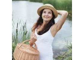 拿着野餐篮子在湖边摆姿势的女人_4962081