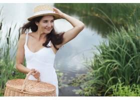 拿着野餐篮子在湖边摆姿势的女人_4962085