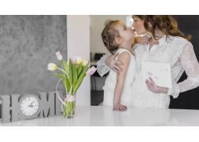年轻的母亲和女儿在家里互相亲吻_4056930