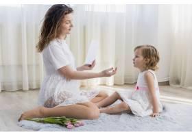 年轻的母亲和她可爱的女儿坐在家里的地毯上_4056828