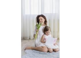 年轻的母亲闻着花香小女儿在家里读贺卡_4056839